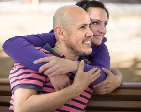 A couple embraces on park bench.