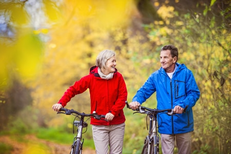 A woman and a man walk their bikes through a park.
