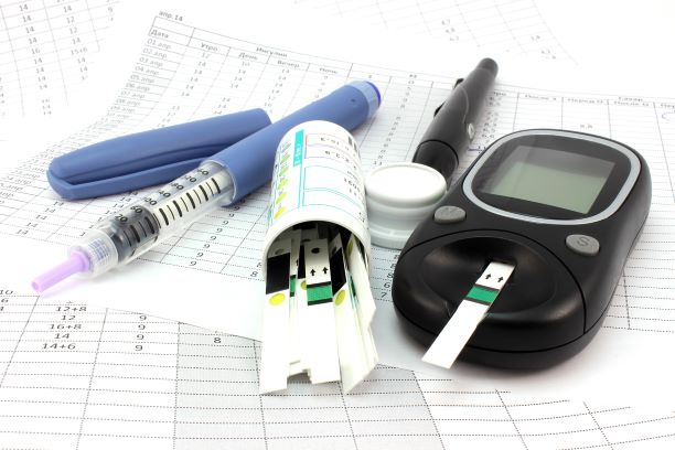 Diabetes supplies on a table, including a lancet, insulin syringe, glucose meter, and test strips.