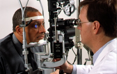 An eye doctor examines a man's eyes for signs of eye disease during a comprehensive eye exam.