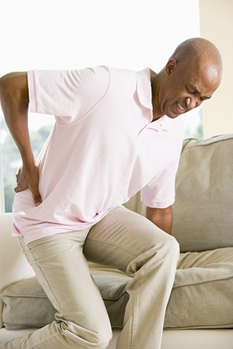 Man standing up from sitting with a hand on his painful hip.