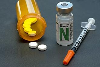 Rezeptflasche mit Pillen; Spritze und Fläschchen mit Insulin.