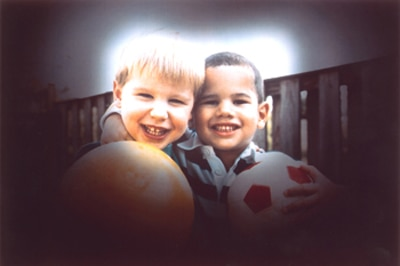 This photo shows how glaucoma affects vision. Shadows darken all sides of a view of two boys. Only the center is bright enough to see clearly.