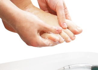 Foto des bloßen Fußes einer Person mit den Händen, welche die Zehen überprüfen.