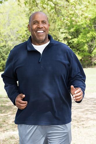An African American man walking briskly in a park
