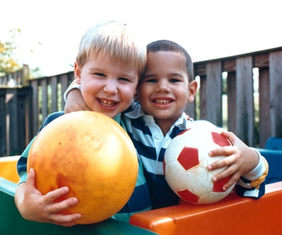 Two boys are holding rubber balls and smiling at the camera.