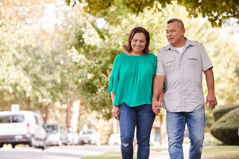 A man and a woman walk together in a park.