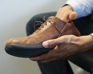 Photo of a man feeling inside his shoe.
