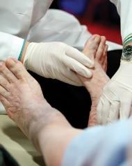 Foto eines Doktors, der bare Füße jemandes überprüft.