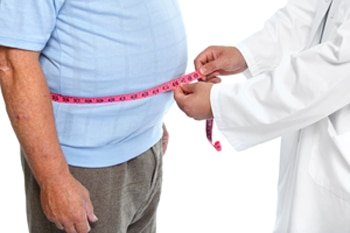 Health care professional measures a man's waistline.