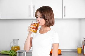 Frau, die ein Glas Apfelsaft trinkt.