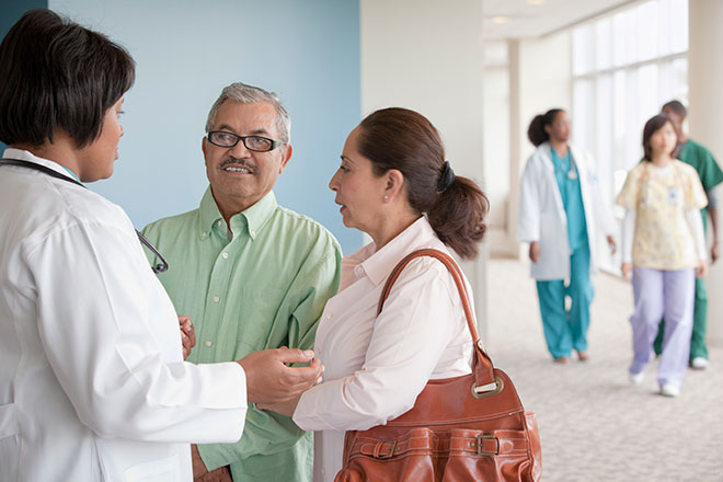 Health care professional talking with a patient and the patient's family member.