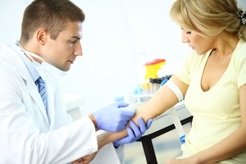 A health care professional drawing blood from a female patient for a blood test.
