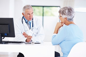Middle-aged woman having a conversation with her doctor in the doctor's office.
