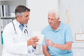 Image of a doctor reviewing paperwork with a patient.