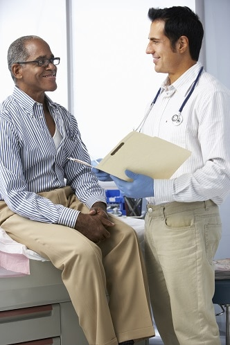 A doctor talking with a male patient who is seated on an examination table.