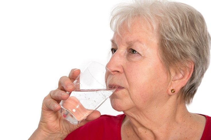 A woman drinking a clear liquid from a glass.