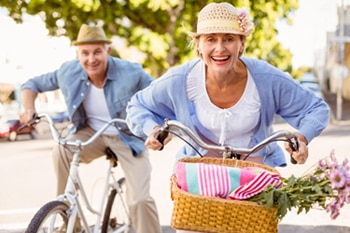 Smiling man and woman riding bikes.