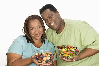 Woman holding a bowl of fruit salad standing next to a man holding a vegetable salad.