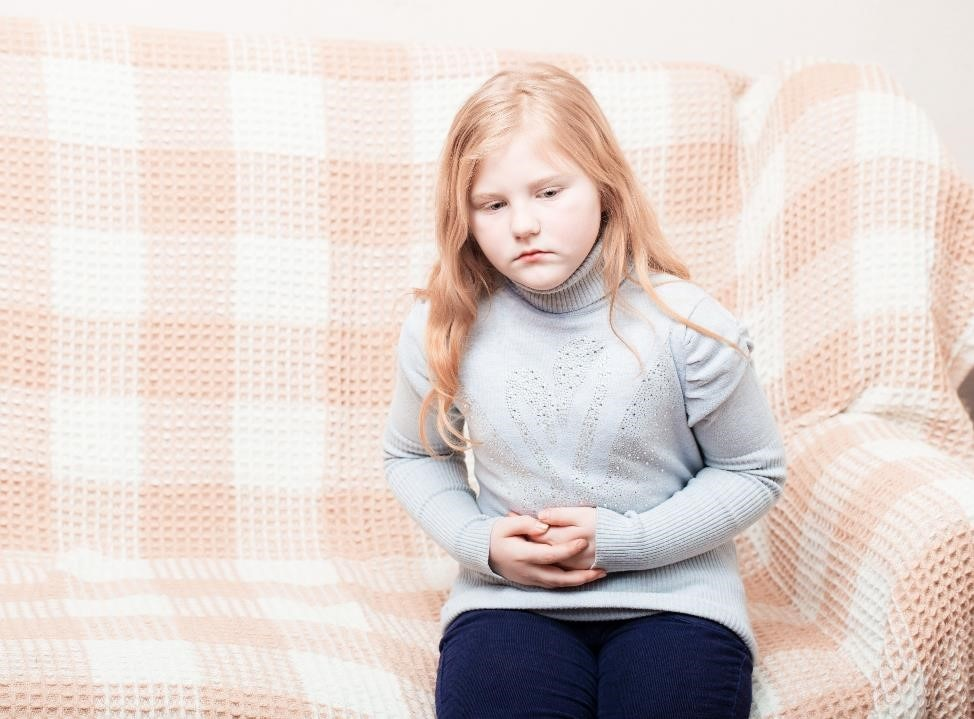 Child sitting on a sofa, holding her abdomen.