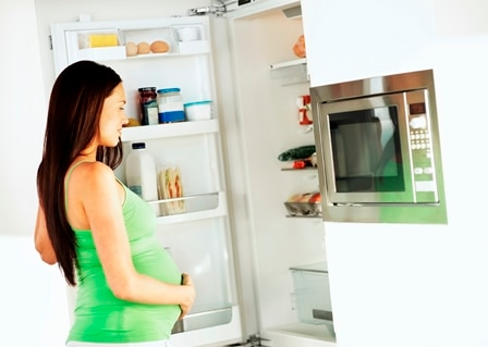 Young pregnant woman looking into the refrigerator