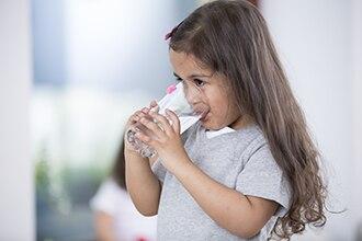Una niña bebe agua de un vaso.