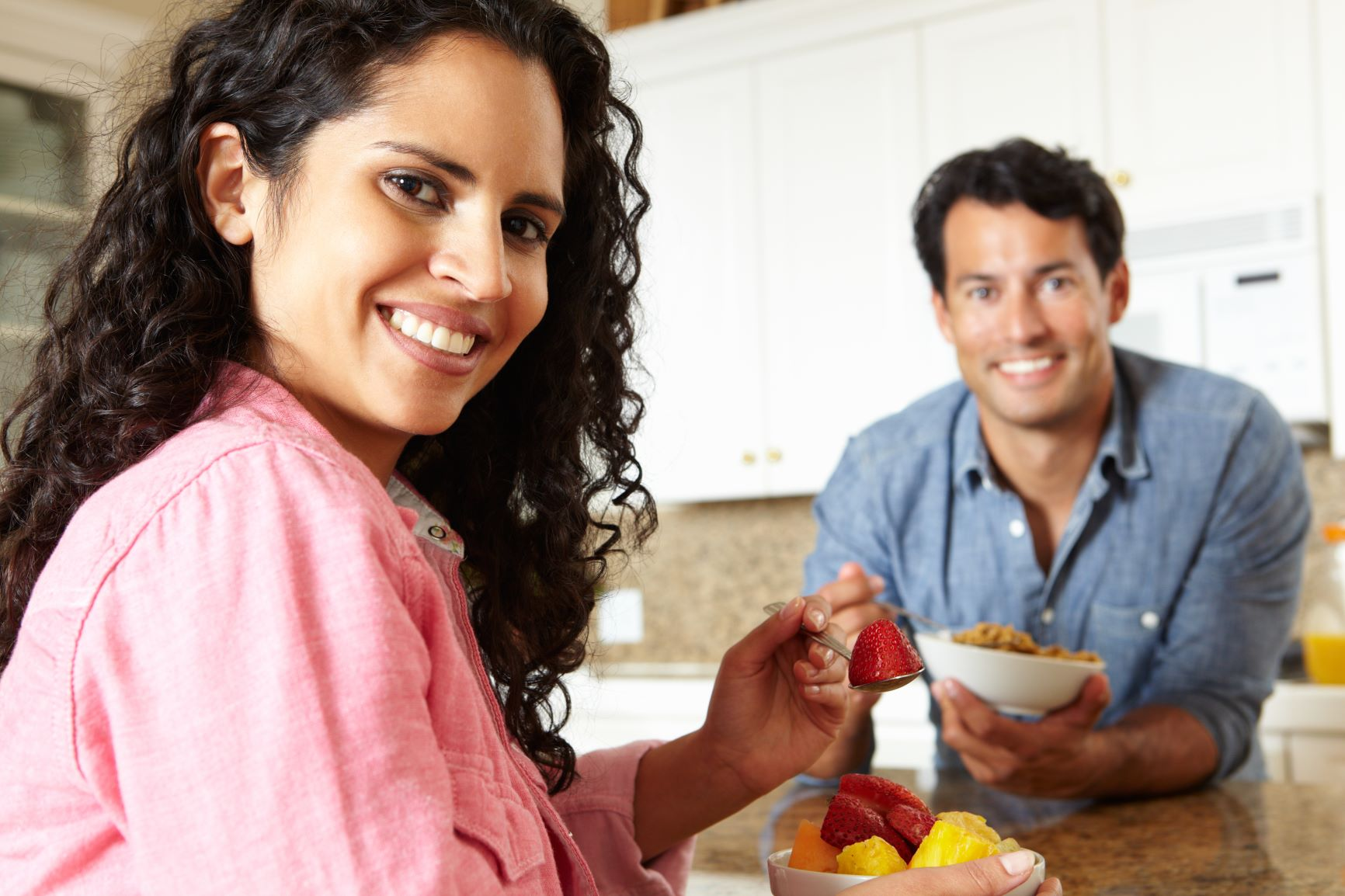Woman eating small bowl of fruit and man eating small bowl of cereal.
