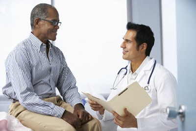 Photo of a male patient talking with a male doctor.
