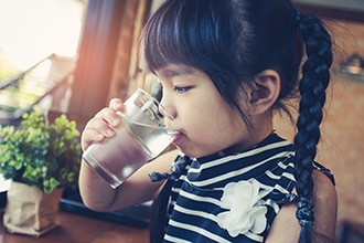 A girl drinks water from a glass.