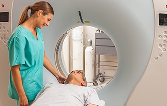 A health care professional speaking to a patient before he enters a magnetic resonance imaging (MRI) machine.
