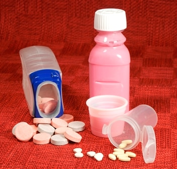 Various antacids are shown in this picture without any brand names (left to right): chewable tablets, pink liquid, and ingestible pills.
