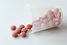 Clear cup of nonsteroidal anti-inflammatory drugs (NSAIDs) spilling out onto table.