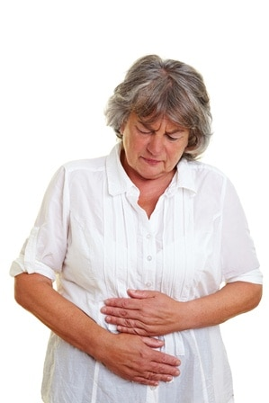Woman clutching her stomach which is in pain.
