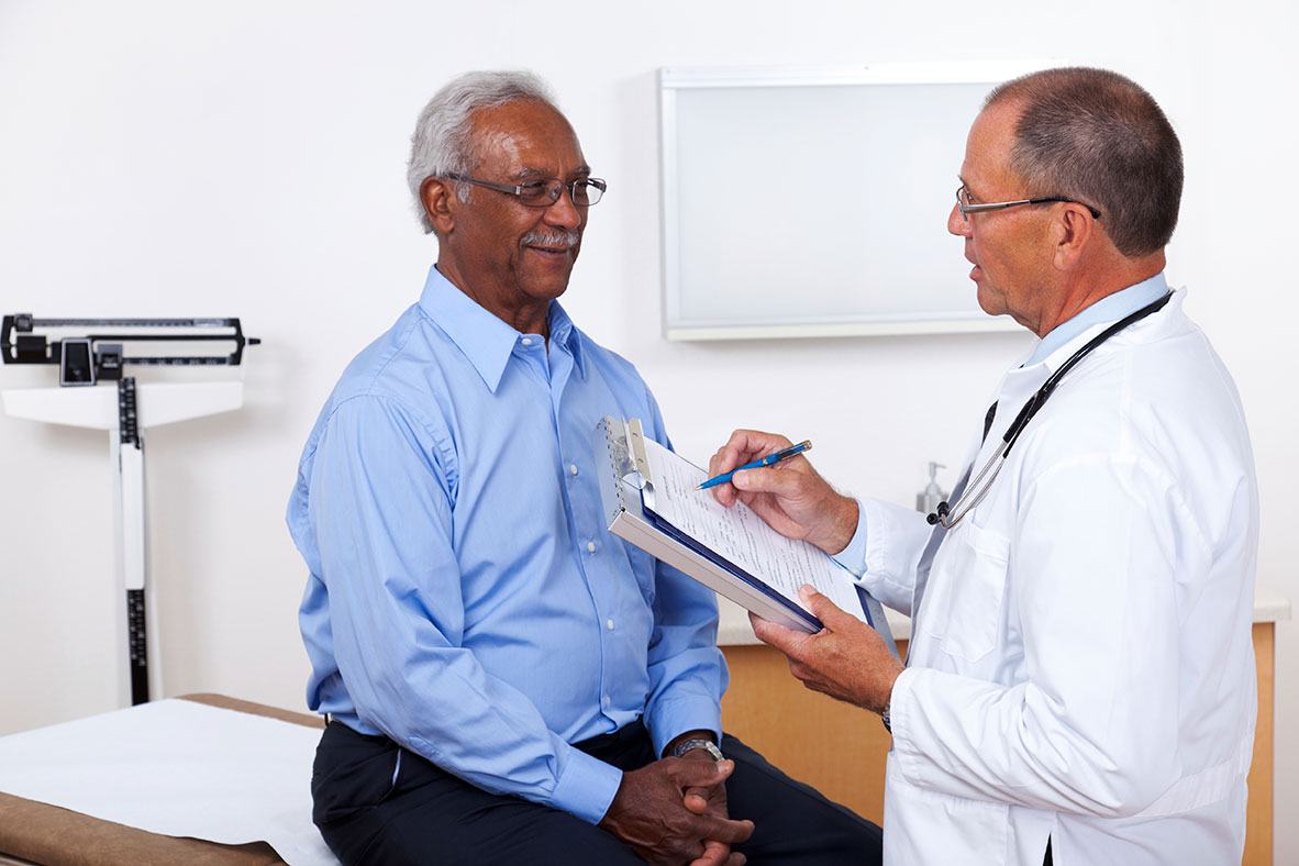 A health care professional speaks with a male patient while taking his medical history.