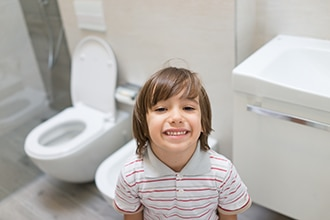 A boy smiles in a bathroom with an open toilet in the background.