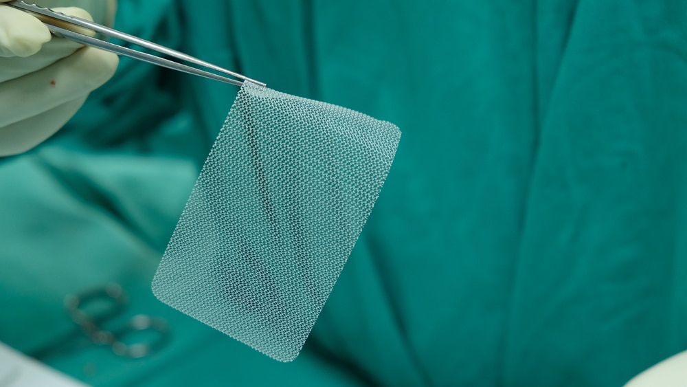 A surgeon using forceps to hold a piece of surgical mesh.