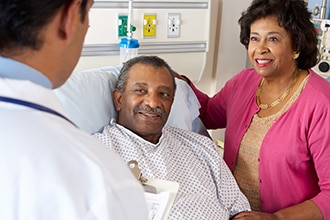 A health care professional speaking to a patient and his wife in a hospital setting.