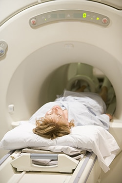 Image of a woman entering a CT Scan machine.