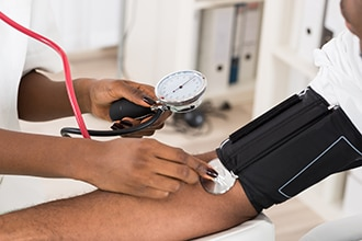 An older man gets his blood pressure taken by a health care professional.