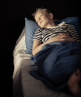 Young boy sleeping in a dark room.