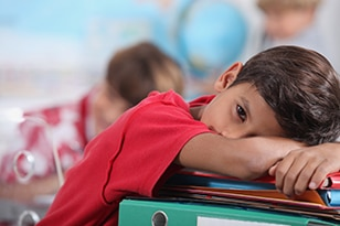 Child with head down on school desk