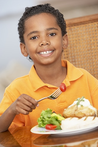 A boy eating a healthy dinner.