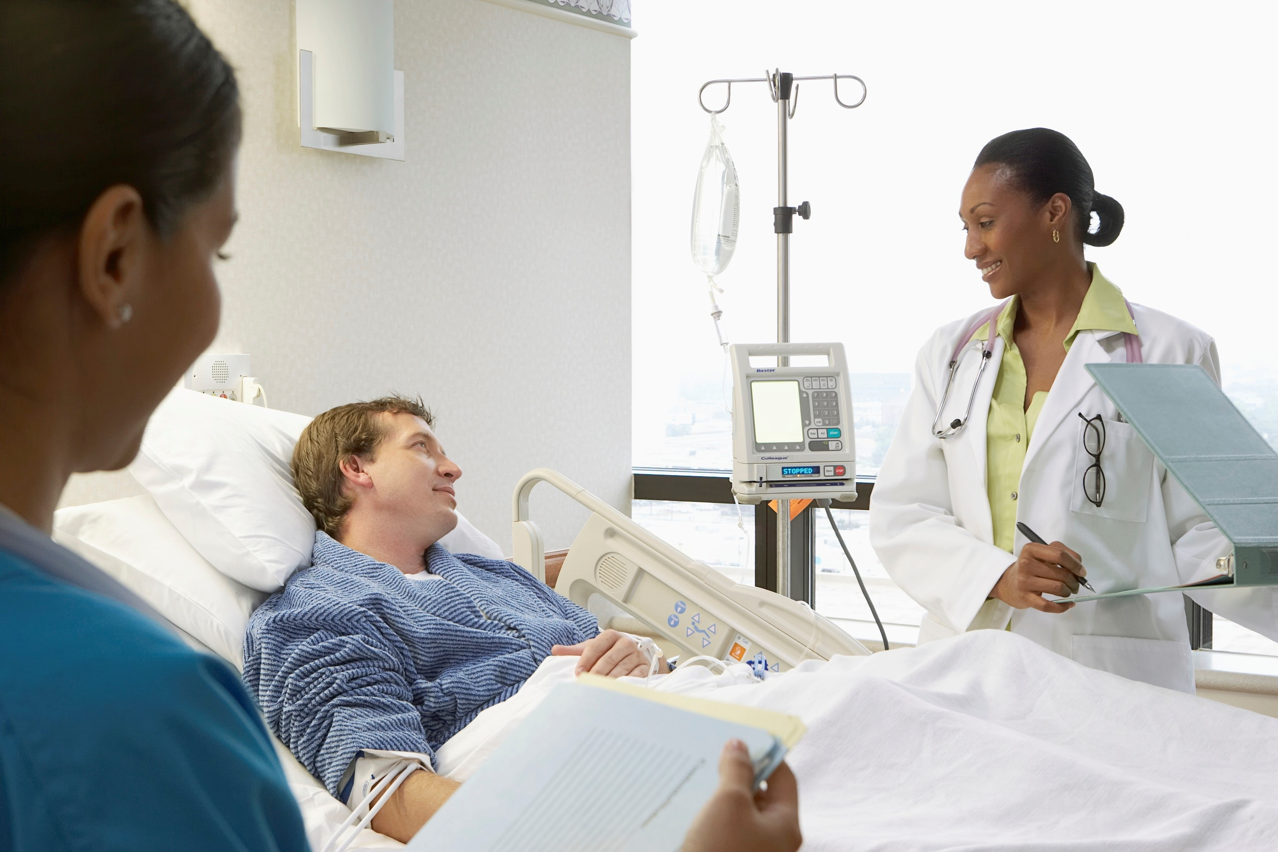 Health care professionals talking with a patient in a hospital bed.
