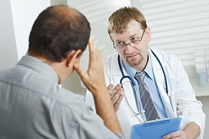 A male doctor talking with male patient about symptoms of proctitis.