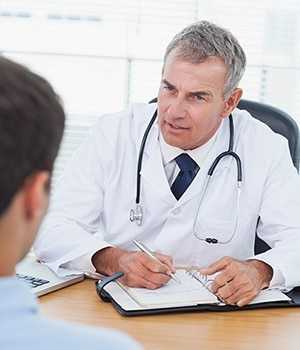 A male doctor sitting at desk writing a prescription for a male patient.