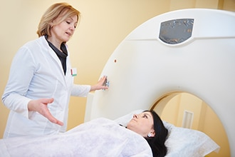 A health care professional speaks to a patient before she enters a magnetic resonance imaging (MRI) machine.