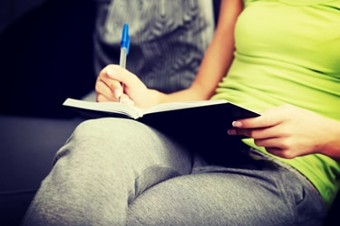 A woman making notes in a food diary.