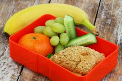 High-fiber foods, including a banana, an orange, grapes, cucumber, and a sandwich on whole wheat bread.