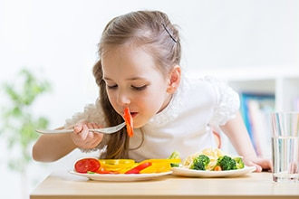 Girl eating a tomato with yellow peppers, broccoli, carrots, and pasta. Photo also shows a glass of water.