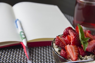 Bowl of strawberries on desk on top of a blank page of a journal book.